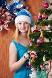 Muchacha en el sombrero de Santa cerca del abeto de la Navidad Foto de archivo libre de regalías