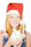 Muchacha en el sombrero de santa con el conejo Fotos de archivo
