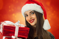 Muchacha en el sombrero de santa con la caja de regalo roja Imágenes de archivo libres de regalías