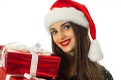 Muchacha en el sombrero de santa con la caja de regalo roja Fotografía de archivo libre de regalías