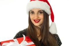 Muchacha en el sombrero de santa con la caja de regalo roja Foto de archivo libre de regalías