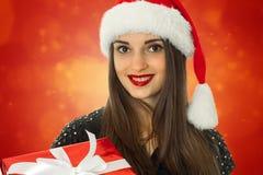Muchacha en el sombrero de santa con la caja de regalo roja Imagen de archivo libre de regalías