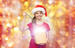 Muchacha en el sombrero de santa con la caja de regalo y la vara de la magia Imagen de archivo libre de regalías