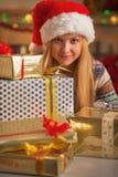 Muchacha en el sombrero de santa con la pila de cajas del regalo de Navidad Imagen de archivo