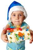 Muchacha en el sombrero de Santa que da hacia fuera s presente Foto de archivo libre de regalías