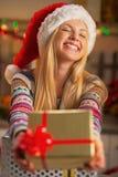 Muchacha en el sombrero de santa que da la caja del regalo de Navidad Foto de archivo