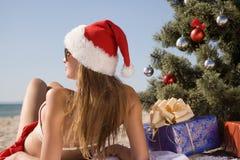 Muchacha en el sombrero de santa que goza del sol mientras que miente en la playa cerca de un árbol de navidad Fotos de archivo libres de regalías