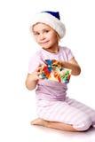 Muchacha en el sombrero de Santa que lleva a cabo un presente Imagenes de archivo