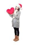Muchacha en el sombrero de Santa que sostiene la almohada del corazón Imágenes de archivo libres de regalías