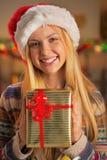 Muchacha en el sombrero de santa que sostiene la caja del regalo de Navidad Fotos de archivo