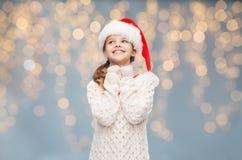 Muchacha en el sombrero de santa que sueña sobre luces de la Navidad Fotografía de archivo libre de regalías