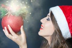 Muchacha en el sombrero de santa, sosteniendo un juguete de la Navidad Año Nuevo Foto de archivo libre de regalías