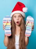 Muchacha en el sombrero de Santas con chancletas Imagenes de archivo
