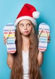Muchacha en el sombrero de Santas con chancletas Imágenes de archivo libres de regalías