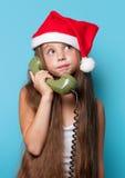 Muchacha en el sombrero de Santas que llama por el teléfono Fotografía de archivo