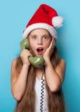 Muchacha en el sombrero de Santas que llama por el teléfono Fotografía de archivo libre de regalías