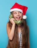 Muchacha en el sombrero de Santas que llama por el teléfono Foto de archivo