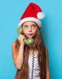 Muchacha en el sombrero de Santas que llama por el teléfono Foto de archivo libre de regalías