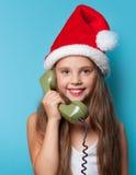Muchacha en el sombrero de Santas que llama por el teléfono Imagenes de archivo