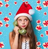 Muchacha en el sombrero de Santas que llama por el teléfono Imágenes de archivo libres de regalías