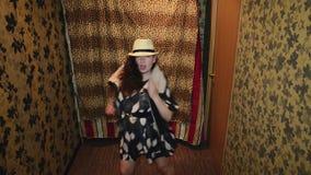 Muchacha en el sombrero de vestido, baile divertido del chaleco de la piel en pasillo parodiar Pelo de la sacudida almacen de metraje de vídeo
