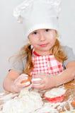 Muchacha en el sombrero del cocinero Fotos de archivo