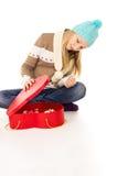 Muchacha en el sombrero del invierno que se sienta con los rectángulos de regalo   Foto de archivo libre de regalías