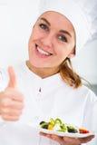 Muchacha en el sombrero del ` s del cocinero y la capa blanca que muestran la ensalada fotos de archivo