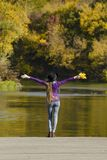 Muchacha en el sombrero que se coloca en el embarcadero con los brazos abiertos Otoño DA soleada Imagenes de archivo