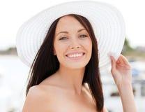 Muchacha en el sombrero que se coloca en la playa Foto de archivo
