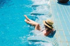 Muchacha en el sombrero que se relaja en el Jacuzzi de la piscina del balneario, disfrutando de vacaciones Forma de vida de Luxut Imagenes de archivo