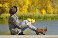 Muchacha en el sombrero que se sienta en el muelle Día del otoño Vista lateral Foto de archivo
