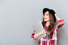 Muchacha en el sombrero que sostiene el ordenador portátil y que mira lejos el copyspace Imagen de archivo libre de regalías