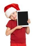 Muchacha en el sombrero rojo de santa con la PC de la tableta en blanco aislada Imagen de archivo