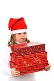 Muchacha en el sombrero rojo de Santa que lleva tres presentes Imágenes de archivo libres de regalías