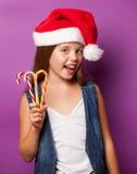 Muchacha en el sombrero rojo de Santas con el caramelo Foto de archivo