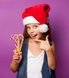 Muchacha en el sombrero rojo de Santas con el caramelo Foto de archivo libre de regalías
