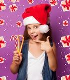 Muchacha en el sombrero rojo de Santas con el caramelo Imagen de archivo