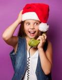 Muchacha en el sombrero rojo de Santas con el microteléfono verde Imagen de archivo libre de regalías