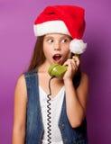 Muchacha en el sombrero rojo de Santas con el microteléfono verde Fotografía de archivo libre de regalías