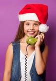 Muchacha en el sombrero rojo de Santas con el microteléfono verde Imagen de archivo