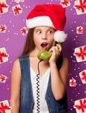 Muchacha en el sombrero rojo de Santas con el microteléfono verde Foto de archivo