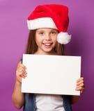 Muchacha en el sombrero rojo de Santas con el tablero blanco Imagen de archivo libre de regalías