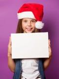 Muchacha en el sombrero rojo de Santas con el tablero blanco Imágenes de archivo libres de regalías