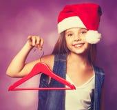 Muchacha en el sombrero rojo de Santas con la suspensión Fotografía de archivo libre de regalías
