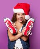 Muchacha en el sombrero rojo de Santas con los gumshoes Foto de archivo libre de regalías