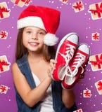 Muchacha en el sombrero rojo de Santas con los gumshoes Imágenes de archivo libres de regalías