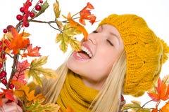 Muchacha en el sombrero y la bufanda que juegan con el ramo del otoño Fotos de archivo