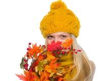 Muchacha en el sombrero y la bufanda que ocultan detrás de ramo del otoño Fotografía de archivo libre de regalías