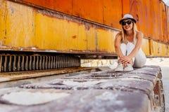 Muchacha en el sombrero y los vidrios que se sientan abrazando sus rodillas imágenes de archivo libres de regalías